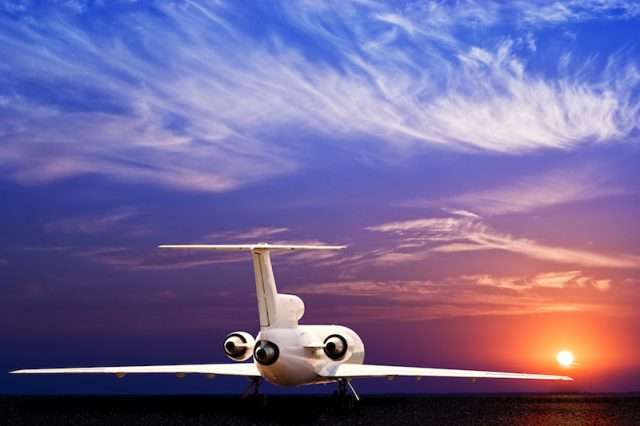 private jet charter about to take off into sunset