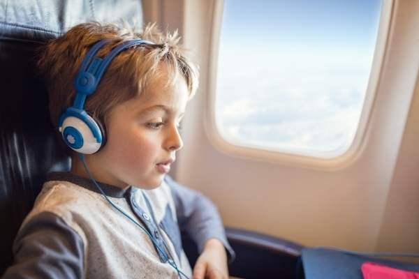 boy with headphones on plane